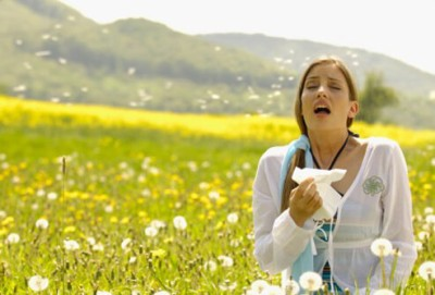 woman sneezing in field